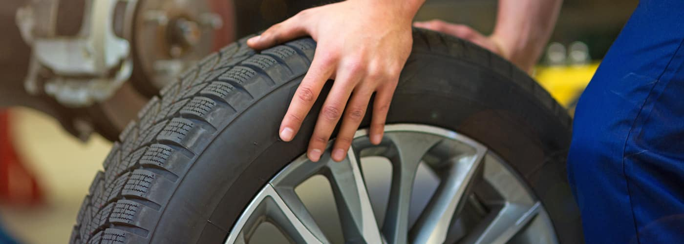 Mechanic hand on tire and wheel