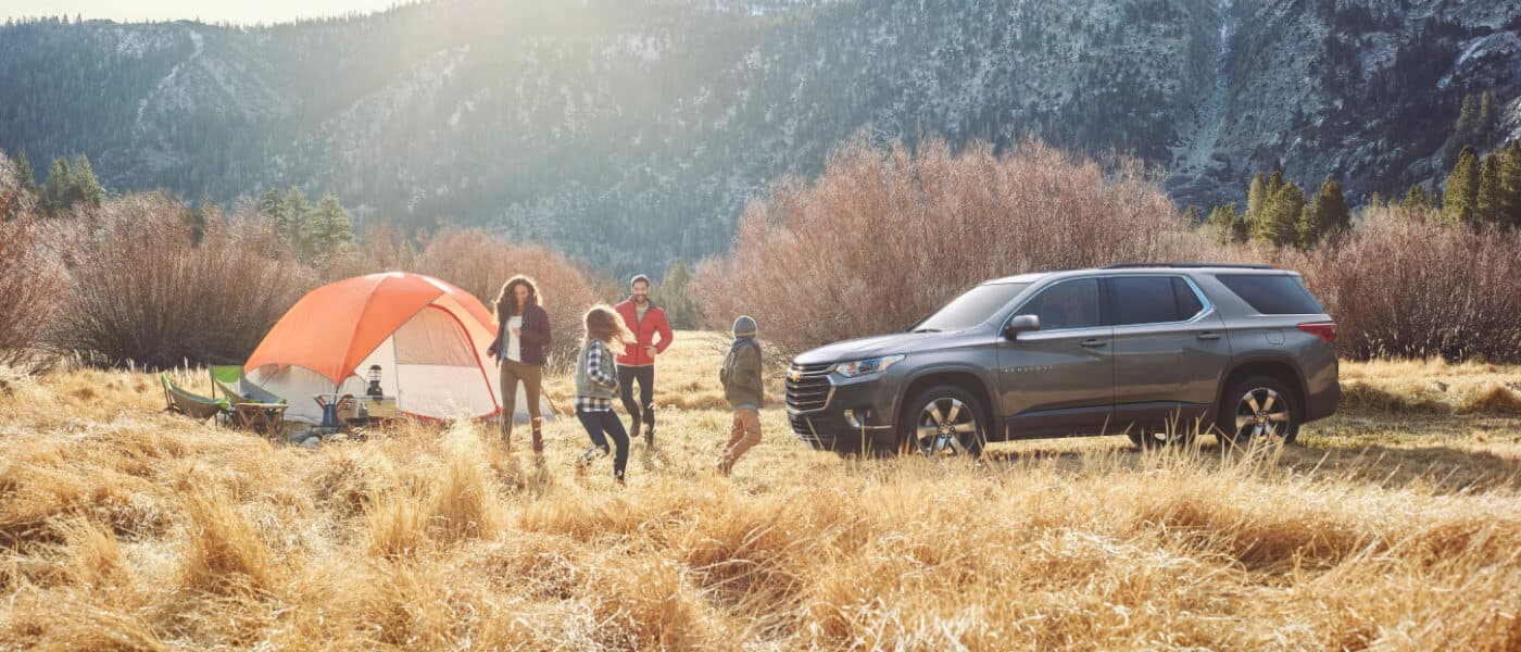 2020 Chevy Traverse parked in a field with a family camping