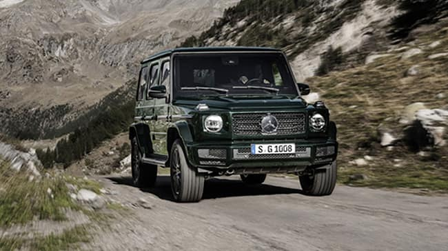 G class driving on dirt path