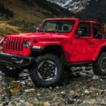 Red Jeep Wrangler parked in the wilderness on a possibly dried up stream bed