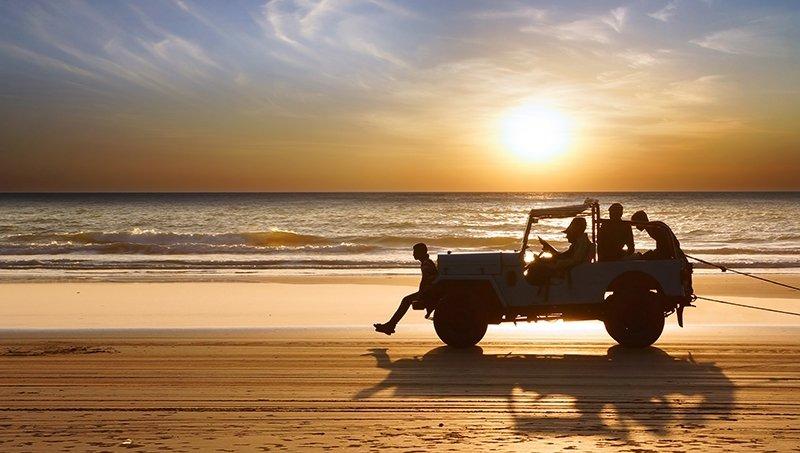 Jeep on beach at sunset
