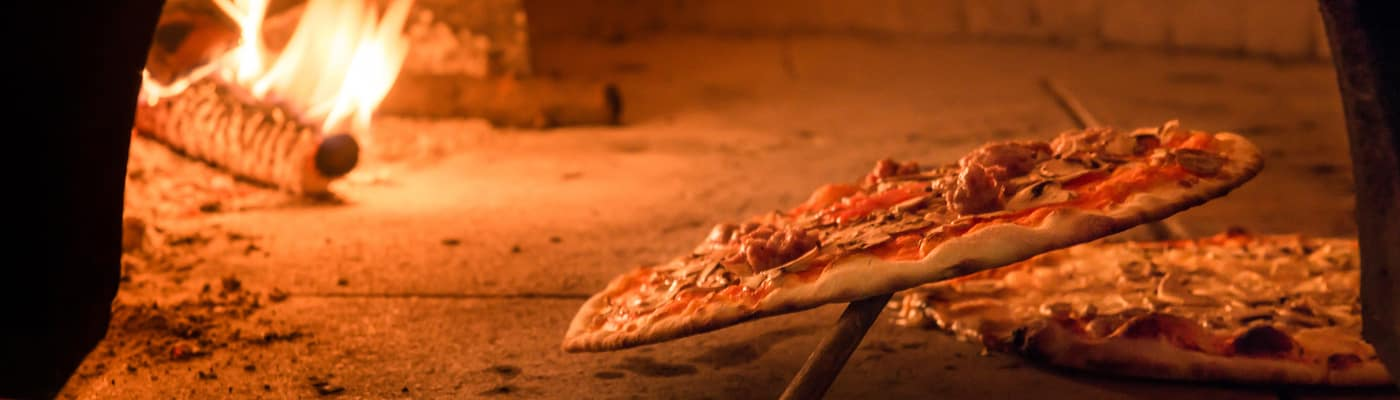 Pizza cooking in a brick oven