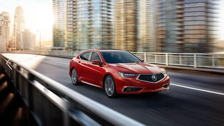Cherry red TLX zips down empty city street