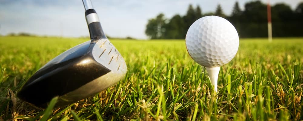 golf ball teed up with golf club on a grassy field