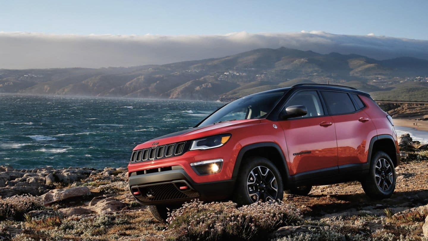 Red 2020 Jeep Compass driving by water