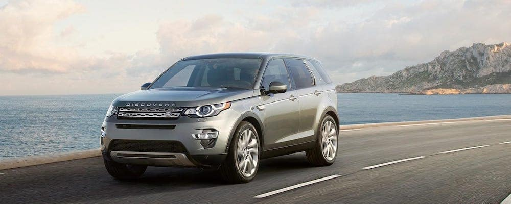 2019 Land Rover Discovery Sport in gray driving on coastal highway with led adaptive headlights