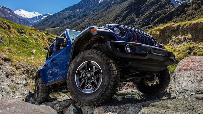 Blue Jeep Wrangler demonstrating Tru Lock system while off-roading on rocky terrain