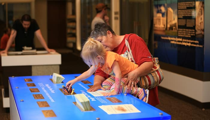 Family enjoying hands-on exhibit at Kansas City Money Museum