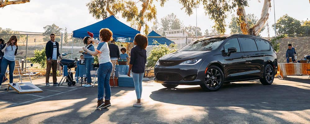 Chrysler Pacifica parked near outdoor party with people playing bags