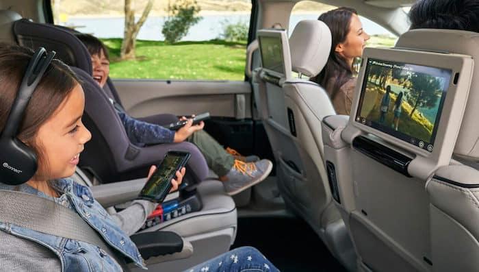 Children enjoying rear seat entertainment system inside Chrysler Pacifica