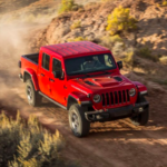 Red Jeep Gladiator descending gravel road on mountain