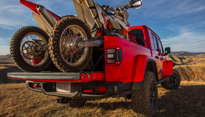 Red Jeep Gladiator carrying two dirt bikes on its flatbed