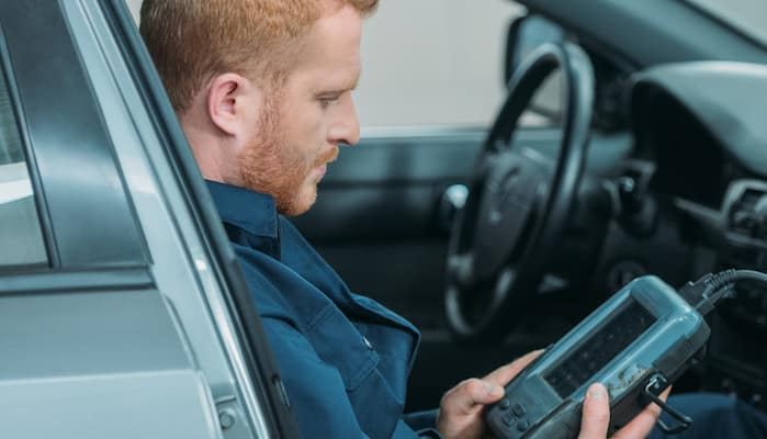 Mechanic looking at diagnostic scanner while sitting inside car