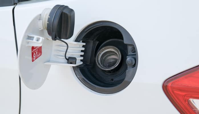Closeup of gas cap and nozzle on white car