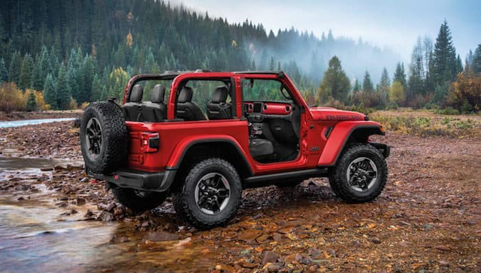 Red Jeep Wrangler driving on rocks near creek in forest