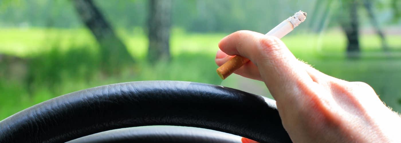 Hand holding cigarette near steering wheel_10384663