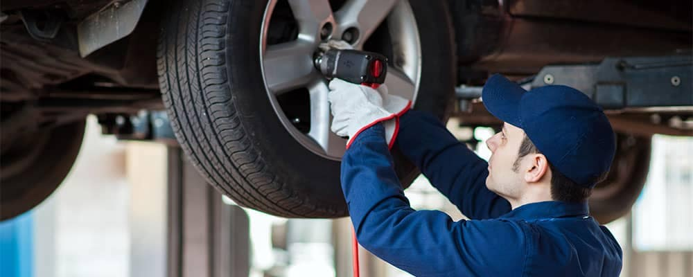 service tech puts tires on vehicle
