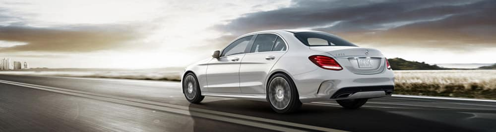 White C-Class sedan driving on open freeway