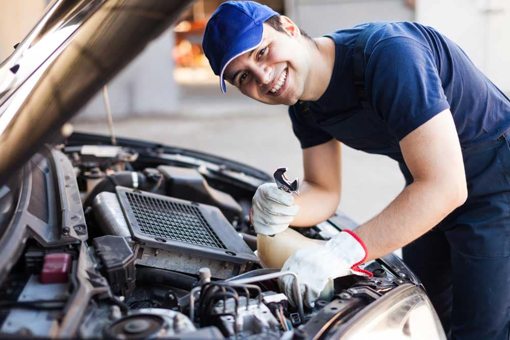 smiling mechanic fixing car