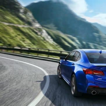 Blue 2018 Acura TLX driving through the mountains