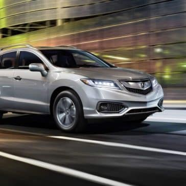 Acura RDX driving on city street at night