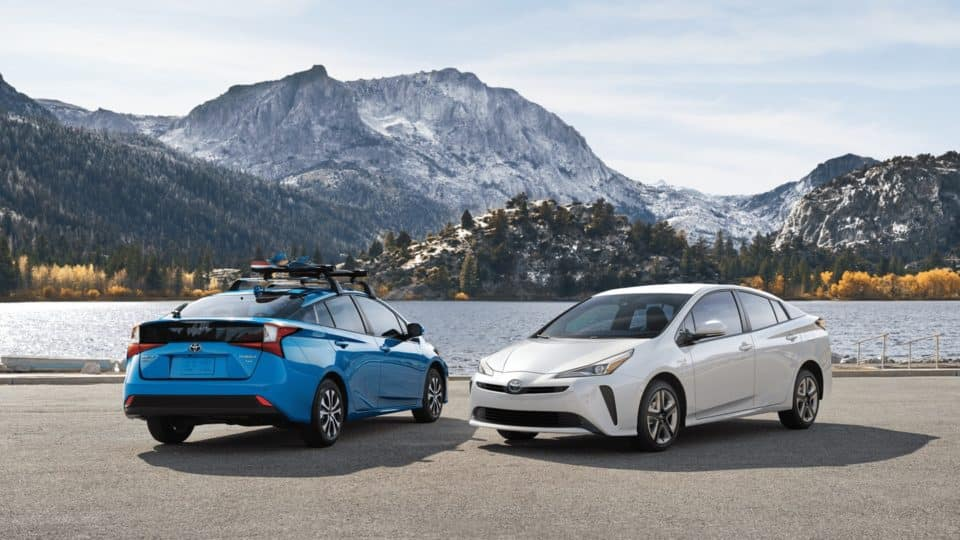 A white 2020 Prius and a blue 2020 Prisu against a mountain and lake.
