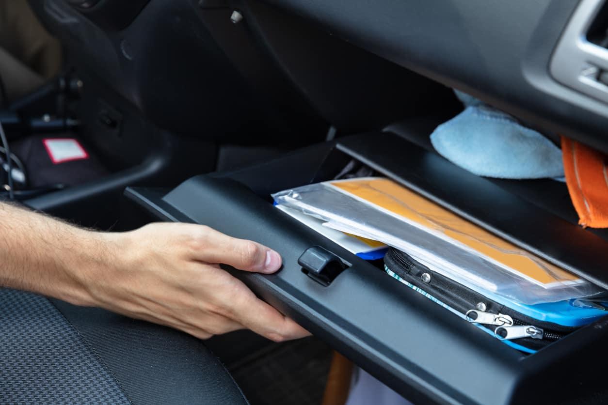 A caucasian hand opening an organized glove box in a car.