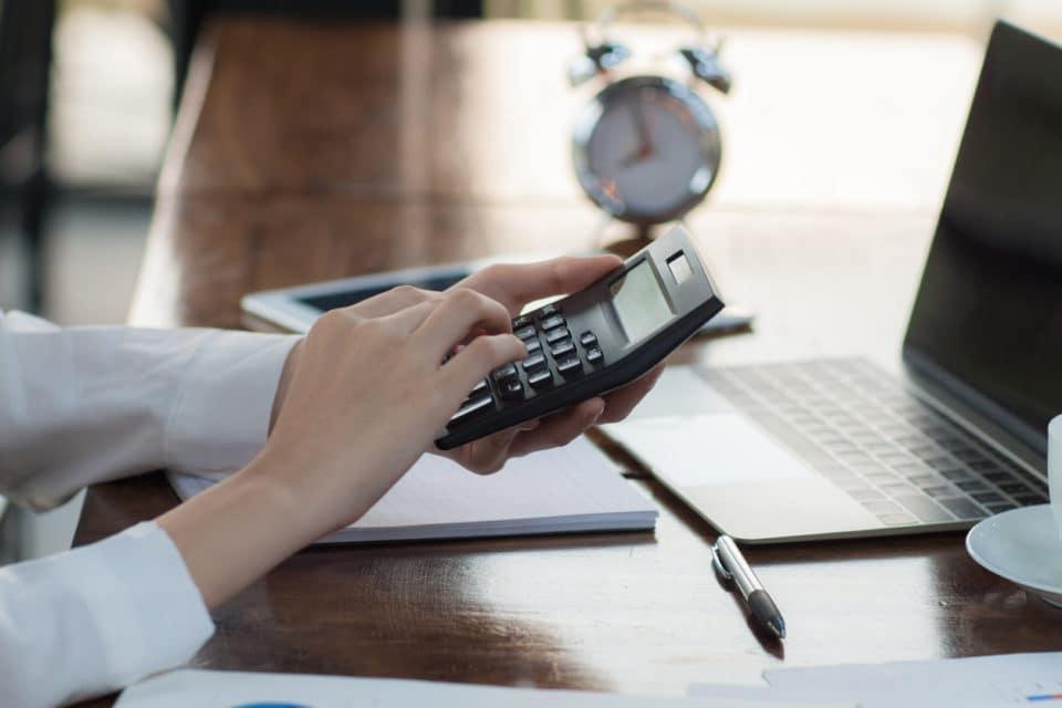 Businesswoman at desk holding a calculator.