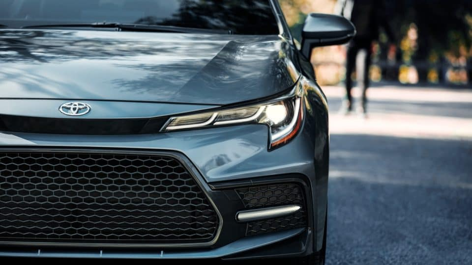 Close-up view of front grille and headlight of a silver 2020 Toyota Corolla