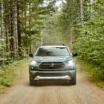 Front view of a blue gray 2020 RAV4 driving through the woods