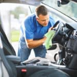A man scrubbing his steering wheel with a microfiber cloth