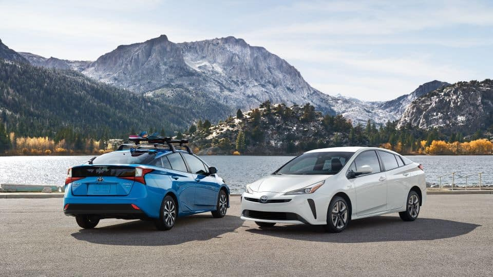 A Blue and a White 2021 Toyota Prius against a mountain and lake.