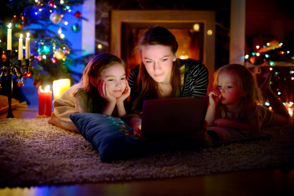 Mother and daughters using laptop with Christmas tree in background