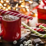 Red mug filled with homemade hot chocolate shot on rustic Christmas table. A red and white candy cane is on the hot chocolate mug and two others candy canes are behind the mug. String Christmas lights and a red gift are out of focus on background. Predominant color is red. DSRL studio photo taken with Canon EOS 5D Mk II and Canon EF 100mm f/2.8L Macro IS USM.