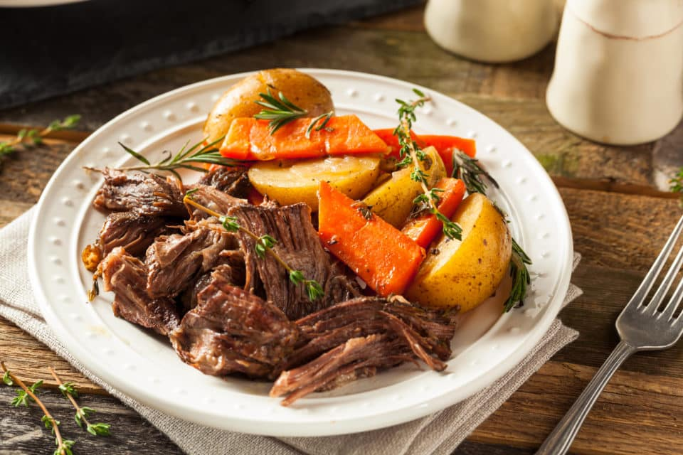 homemade pot roast with carrots and potatoes in a white bowl.