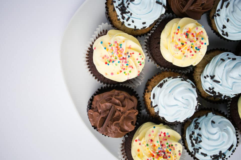 nine chocolate cupcakes on a white plate on a white background. One cupcake has chocolate frosting, two have yellow frosting, and four have blue frosting.