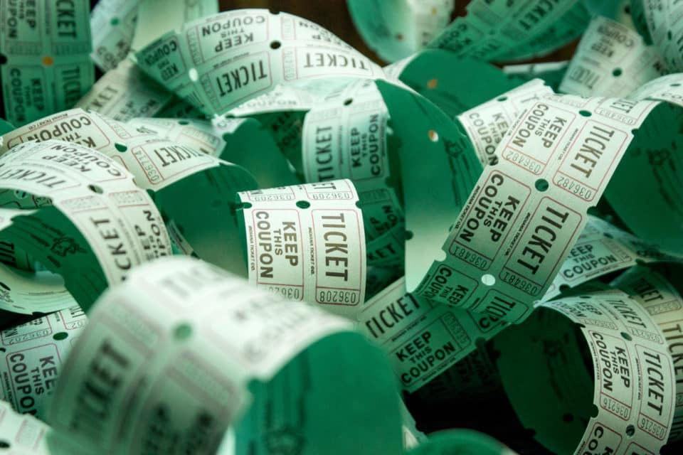 Roll of green admit one coupon raffle tickets for lottery or raffles of charity