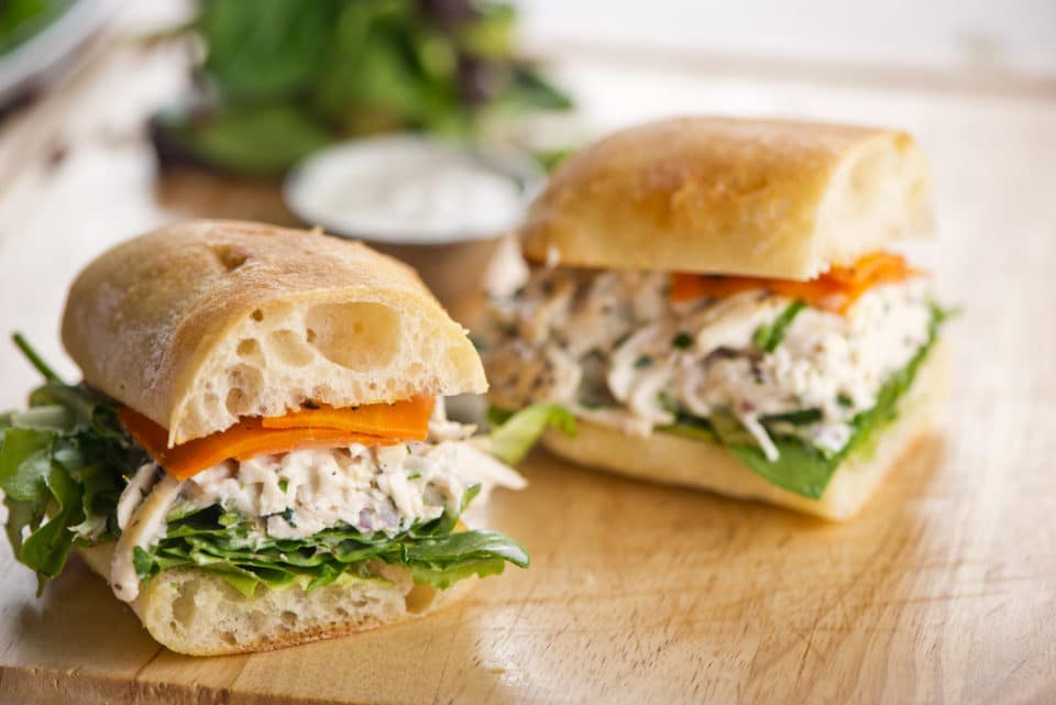Chicken salad sandwich served on toasted whole baguette with melted Swiss cheese, sautéed onions, lettuce, tomato, mayonnaise and seasoned salt and pepper.