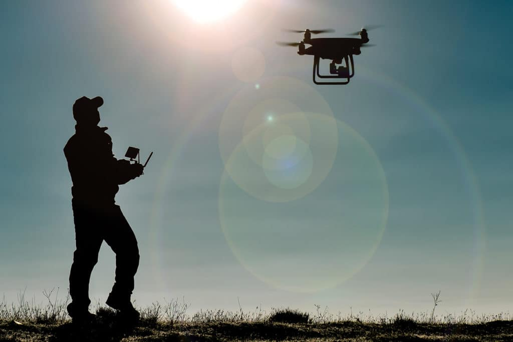 silhouette of man flying drone