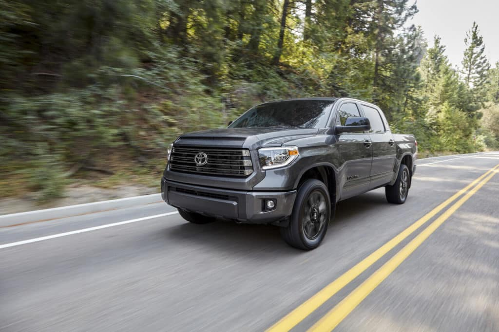 Grey Tundra truck on the road through a wooded area