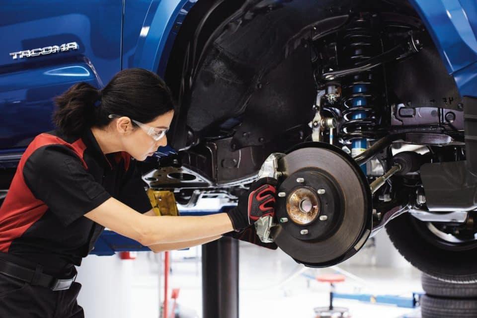 A Toyota service technician doing brake work on a blue Toyota Tacoma truck