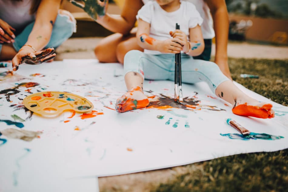 Family painting a white sheet in the yard