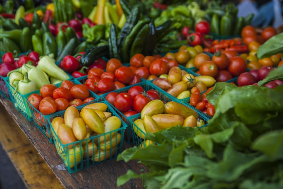 Vegetables with various tomatoes, pimentos and lettuce on market stall.