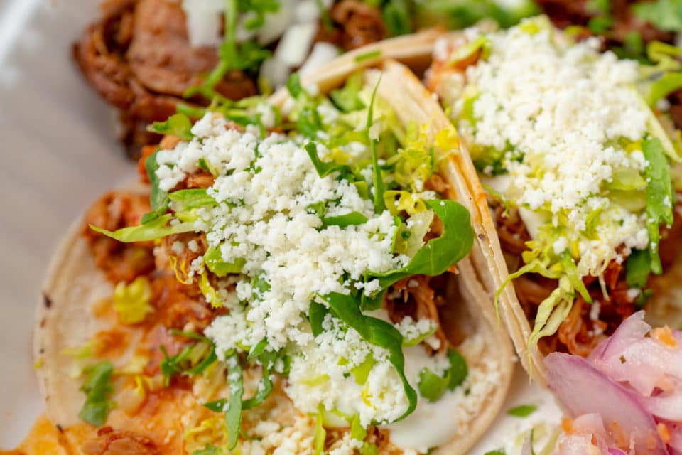 Close-up of tacos with chicken, cheese, with pickled onions and lime wedges