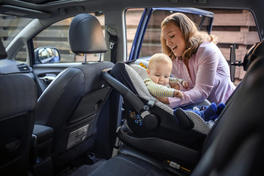 Mother putting her child in a car safety seat