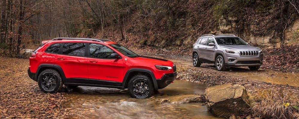 Two Jeep Cherokees out in the woods, one red, one silver.