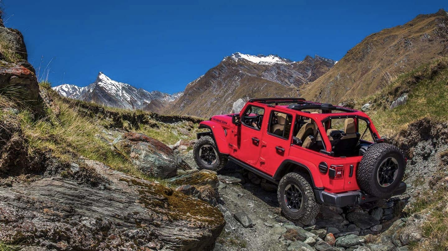 2020 Jeep Wrangler red driving up mountain