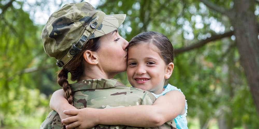 Female soldier hugging her child