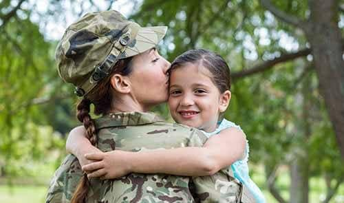 Female soldier hugging daughter