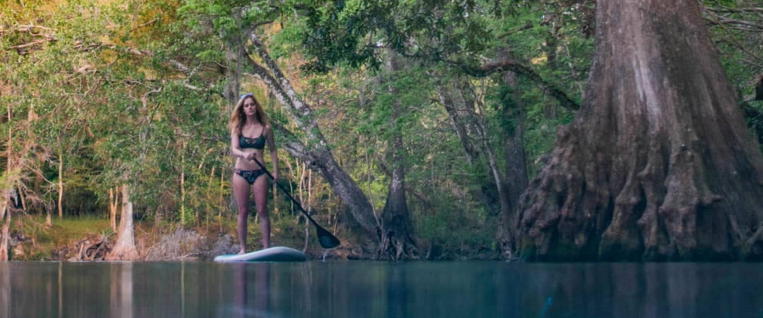 woman paddle boards at Ginnie Springs
